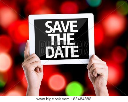 Tablet pc with text Save the Date with bokeh background