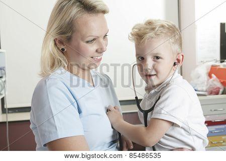 Female doctor using stethoscope to examining little sweet boy
