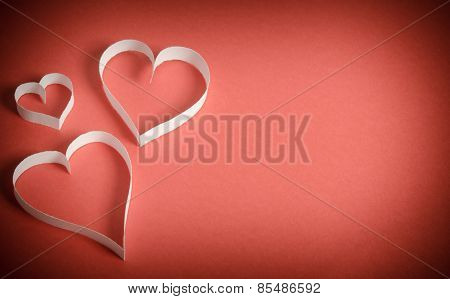 Three Hearts Of White Paper Lying On A Red Background