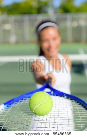 Tennis. Woman tennis player showing ball and racket on tennis court outside. Female tennis player.