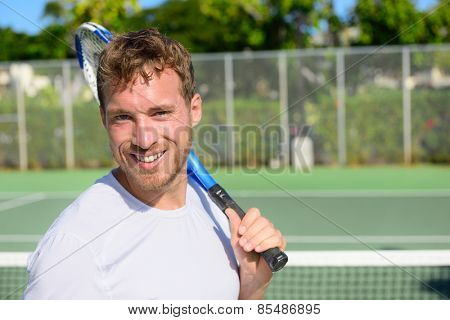 Portrait of male tennis player holding tennis racket after playing at game outside on hard court in summer. Fit man sport fitness athlete smiling happy living healthy active lifestyle outside.