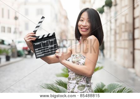 Young Asian Woman Smiling Showing Clapper Board