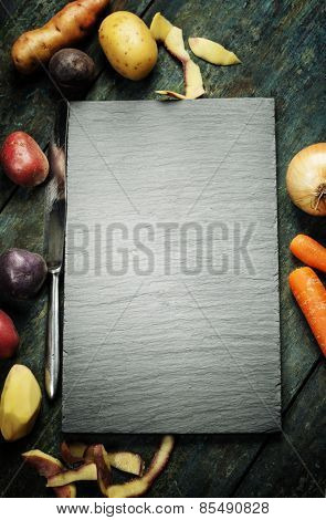 Food background, with fresh vegetables. Slate and wood background.