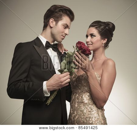 Husband offering his beautiful wife a bunch of red roses, they are looking at each other.