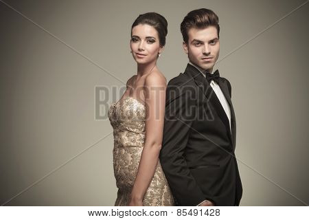 Elegant man and woman standing back to back on grey studio background.