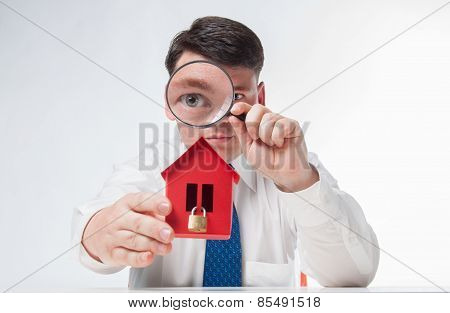Man with a magnifying glass and paper house