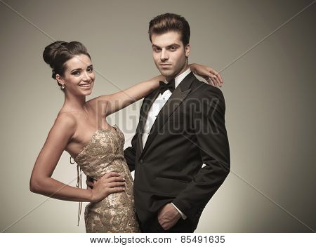Side view of a happy elegant couple embraing while smiling and looking at the camera.