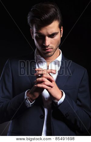 Elegant young business man looking down while holding his hand together, praying.