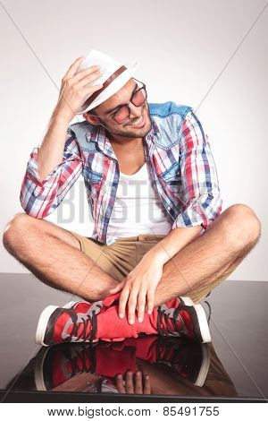 Casual fashion man sitting with his legs crossed while looking away from the camera. He is holding his right hand on his hat.