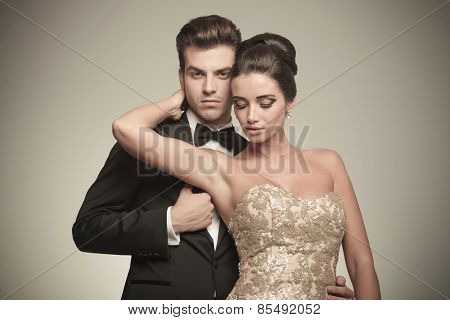 Elegant woman looking down while holding her hand around her husbands neck.