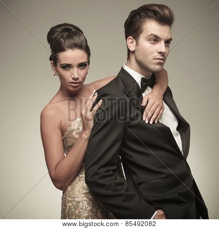 Side view of a handsome elegant man looking away while his wife is embracing him.