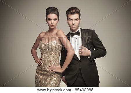 Attractive elegant man fixing his jacket while his lover is holding her hand around her waist.