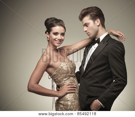 Handsome young man holding his lover and looking at her while she is smiling at the camera.