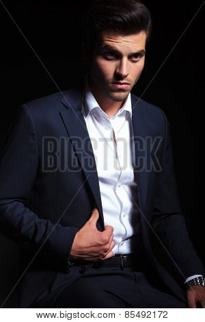 Attractive young business man sitting while fixing his jacket, lookinng away from the camera.
