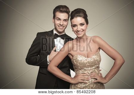 Happy elegant couple laughing while looking at the camera.