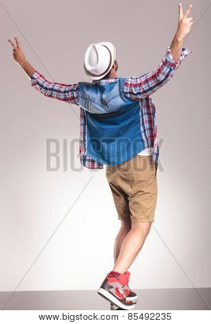 Back view of a young casual man celebrating a victory by holding his hands up..