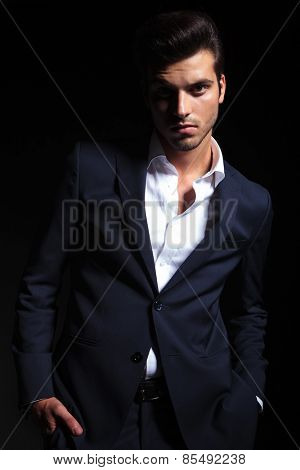 Portrait of a young handsome business man posing on black studio background with his hands in pockets.