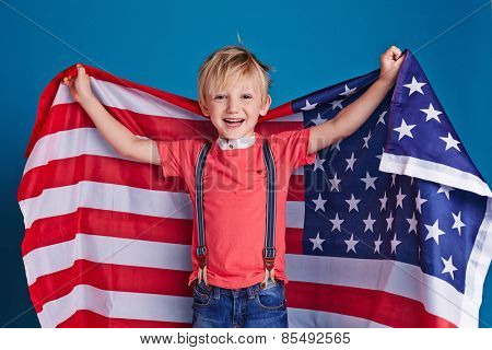 Little boy cheering with American flag