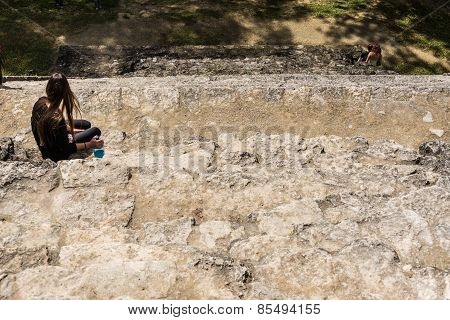 Young Women Resting On  Mayan Steps Ruins At Tikal, National Park. Traveling Guatemala, Central Amer
