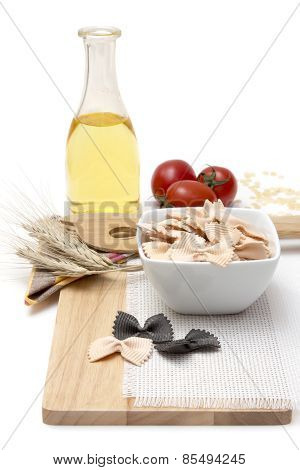 Italian Pasta, Macaroni Farfalle With Cherry Tomatoes And Olive Oil In A Glass Bottle