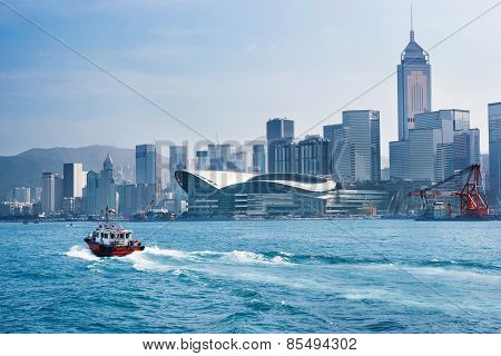 Red Tug Boat In Front Of Hong Kong Skyline