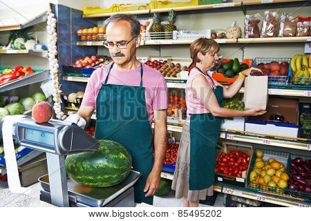 adult senior sale man with assistant in fruit vegetable market shopping store