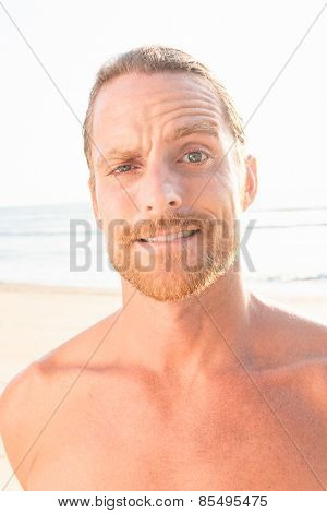 Close up Portrait of Handsome Man with Beard and Mustache at the Beach Looking at the Camera with Confused Face.