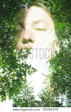 Double exposure portrait of attractive lady combined with photograph of tree