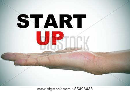 the hand of a young man holding the text start up