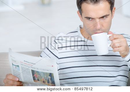 Man drinking coffee whilst reading the newspaper