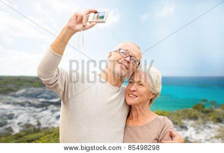 age, tourism, travel, technology and people concept - senior couple with camera taking selfie on street over beach background