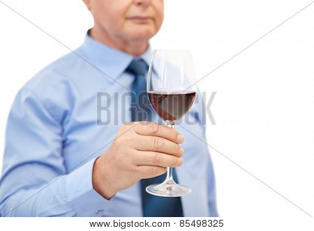profession, winery, drinks, holidays and people concept - close up of senior man holding glass with red wine