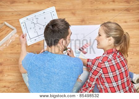 design, repair, decoration and people concept - happy couple with blueprint and color samples sitting on floor at home
