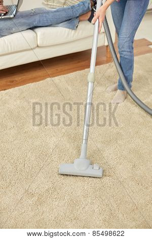 people, housework and housekeeping concept - close up of couple legs and vacuum cleaner on carpet at home