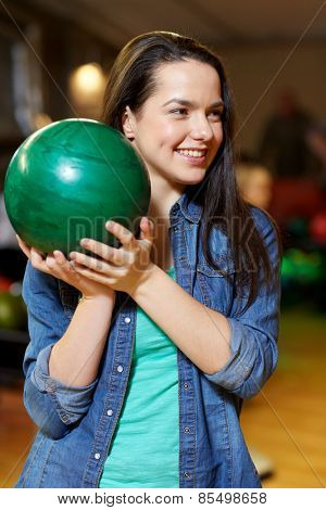 people, leisure, sport and entertainment concept - happy young woman holding ball in bowling club