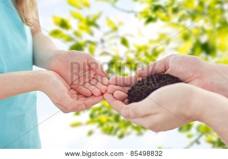 people, charity, family and legacy concept - close up of father and girl holding soil in cupped hands over green nature background