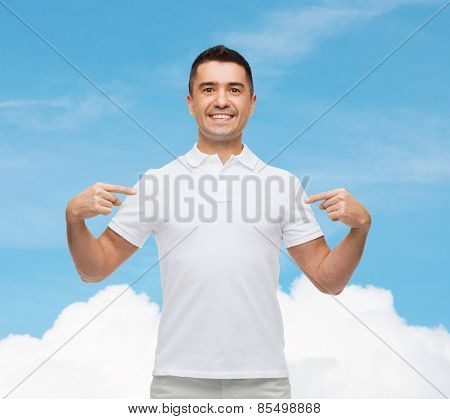 happiness, advertisement, fashion, gesture and people concept - smiling man in t-shirt pointing fingers on himself over blue sky and cloud background