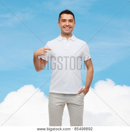 happiness, advertisement, fashion, gesture and people concept - smiling man in t-shirt pointing finger on himself over blue sky and cloud background