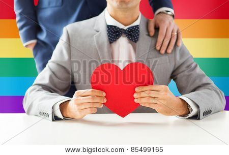 people, homosexuality, same-sex marriage, valentines day and love concept - close up of happy married male gay couple with red paper heart shape on wedding over rainbow flag background