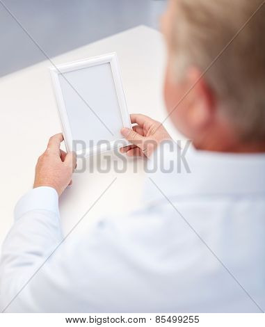 oldness, memories, loneliness and people concept - close up of old man holding blank photo frame