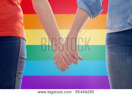 people, homosexuality, same-sex marriage, gay and love concept - close up of happy lesbian couple holding hands over rainbow flag background