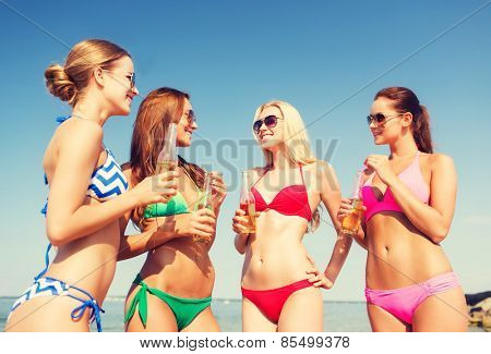 summer vacation, holidays, travel and people concept - group of smiling young women sunbathing and drinking on beach