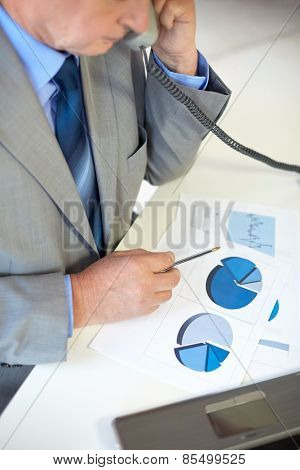 business, people and communication concept - close up of senior businessman with charts and papers calling on telephone