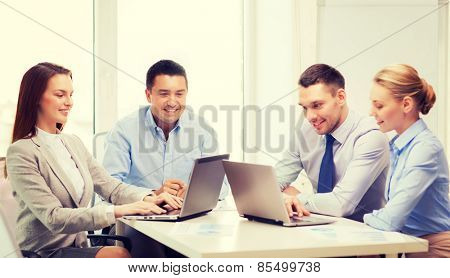 business and office concept - smiling business team working with laptop computers in office