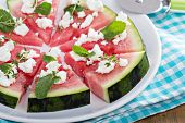 stock photo of watermelon  - Watermelon pizza with crumbled feta cheese and herbs - JPG