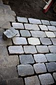stock photo of cobblestone  - Paving a street in the city with old cobblestone - JPG