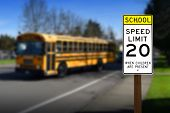 foto of mph  - School zone speed limit sign with bus driving down the road on a sunny day - JPG