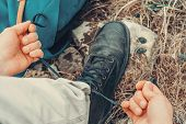 picture of pov  - Hiker man tying shoelaces on nature outdoor near backpack - JPG
