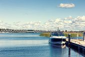 image of dock  - The boat is at the dock on the river against the background of the railway bridge across the river on a summer day - JPG