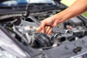 foto of garage  - Hand of car mechanic with wrench - JPG